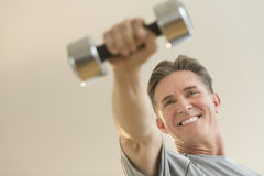 Happy Man Lifting Dumbbell Against Beige Background Stock Photo