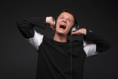 Happy man listening to music. On headphones, black background Stock Images