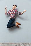 Happy man listening to music from cell phone and jumping. Happy excited young man listening to music from cell phone and jumping over grey background Stock Photos