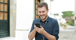 Happy man listening to music from a cellphone in the street. Happy man listening to music from a cellphone walking in the street of a town stock footage