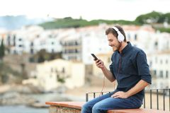 Happy man listening to music on a ledge. Happy man wearing headphones listening to music on a ledge with a town in the background stock photography