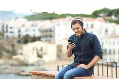 Happy man listening to music on a ledge in a town royalty free stock image