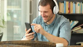 Happy man listening to music on phone in a bar. Happy man listening to music on smart phone sitting in a coffee shop stock video footage