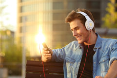 Happy man listening to music from a smart phone. With a warmth sunset city background royalty free stock photography