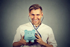 Happy man listening to piggy bank with stethoscope. Happy successful man listening to piggy bank with stethoscope Royalty Free Stock Photos