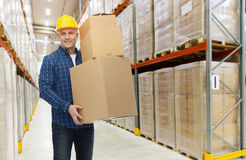 Happy man or loader with box at warehouse Stock Photography