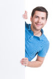 Happy man look out from blank banner. Happy young man look out from blank banner - isolated on white Stock Photography