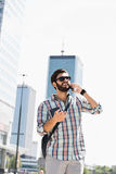 Happy man looking away while using cell phone in city Royalty Free Stock Photos