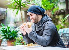Happy man looking at a burger and sandwich Royalty Free Stock Image