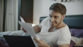Happy man looking business papers at home. Successful businessman waving yes stock video