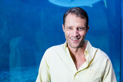Happy man looking at camera beside the fish tank Stock Images