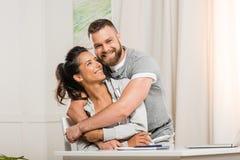 Happy man looking at camera while hugging woman royalty free stock photo