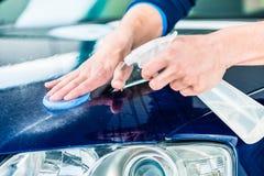 Happy man looking at camera while waxing a blue car. Happy young man looking at camera while waxing a blue car outdoors at car wash Royalty Free Stock Photos