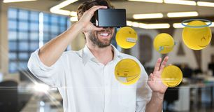 Happy man looking at emojis on VR glasses. Digital composite of Happy man looking at emojis on VR glasses Stock Photography