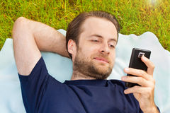 Happy man looking at mobile phone while laying on grass Stock Photography