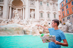 Happy man looking at touristic citymap near Trevi Fountain, Rome, Italy. Caucasian boy near fountain Fontana di Trevi with city map Royalty Free Stock Photography