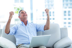 Happy man looking up while working on laptop Royalty Free Stock Photo