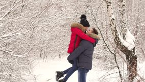 Portrait of a couple in love in the winter forest. A happy man in love lifts his wife in the park among a multitude of snow-covered trees. A loving happy couple stock footage