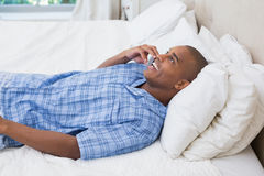 Happy man lying on bed and talking on phone Royalty Free Stock Images