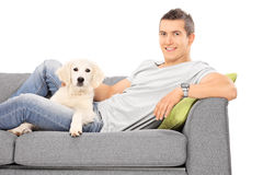 Happy man lying on couch with a puppy Stock Photos