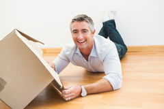 Happy man lying on floor with box looking at camera Stock Photo