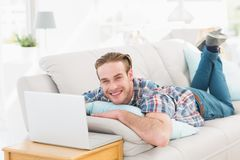 Happy man lying on sofa using laptop Royalty Free Stock Photography