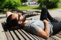 Happy man lying on street bench or sun bed Stock Image