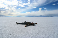 Happy man lying on the surface of Salar de Uyuni,  Royalty Free Stock Photography