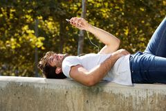 Happy man lying on wall in park with cellphone Stock Images