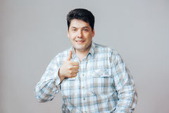 Happy man makes a gesture thumb up, portrait on white background Royalty Free Stock Image