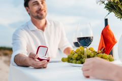 Happy man making propose with ring to girlfriend. In romantic date stock photos