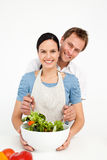 Happy man mixing a salad with his girlfriend royalty free stock images