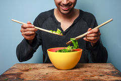 Happy man mixing salad with wooden spoons Royalty Free Stock Photo