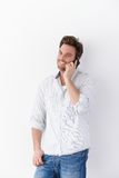 Happy man on mobile phone. Happy young man using mobile phone, standing over white background, smiling Stock Photography