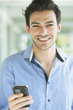 Happy man with mobile phone. Happy young latin man with cell phone, sending text message Royalty Free Stock Images