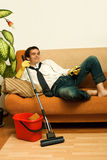 Happy man with mop. Happy man enjoying a tv show meantime of cleaning the room stock photography