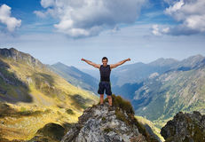 Happy man on mountain cliff Stock Images