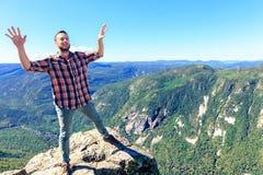 Happy man on mountain summit. stock image