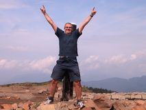 Happy man in the mountain top. Victorious man in a top of a mountain Royalty Free Stock Photo