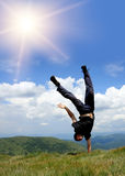 Happy man in mountains. Stay head over heels on hand royalty free stock image