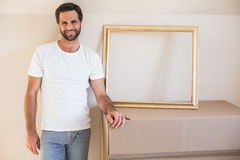 Happy man with moving boxes and frame Stock Images