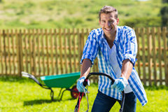 Happy man mowing lawn Stock Photos