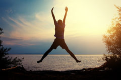 Happy Man at the Nature. Toned Photo of Happy Person jumping on the Sunset Background stock images