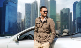 Happy man near cabriolet car over city background Stock Image