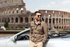 Happy man near cabriolet car over coliseum Royalty Free Stock Photo