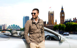 Happy man near cabriolet car over london city. Travel, tourism, transport, leisure and people concept - happy man near cabriolet car over london city background Royalty Free Stock Image