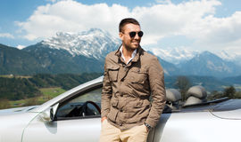 Happy man near cabriolet car over mountains Stock Photo