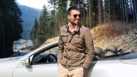Happy man near cabriolet car over nature Stock Images