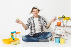 Happy man in newspaper hat holds supermarket grocery push carts for shopping. Instruments for renovation apartment. Isolated on white background. Wallpaper stock images