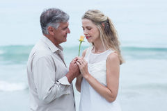 Happy man offering flower to his girlfriend Royalty Free Stock Images